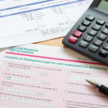 Photo of a UK self assessment tax return with calculator and pay