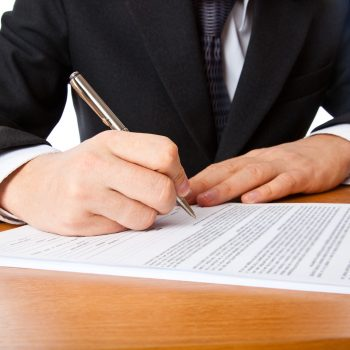 Close up on a businessman hands signing a contract. Isolated on