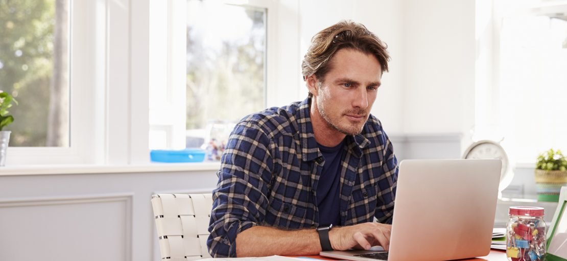 Man Sitting At Desk Working At Laptop In Home Office