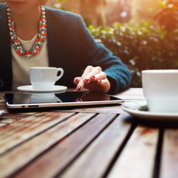 Portrait of a young business lady sitting in cafe working on a t