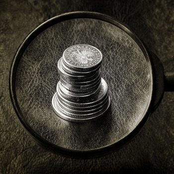 How to Maximise a Business, with Almost No Money Magnifying Glass over stack of coins