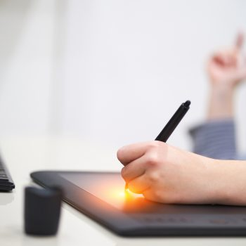 Closeup hands of female illustrator designer, holding pen and painting on computer graphic tablet. Freelance concept The Top Freelance Roles So Far in 2019
