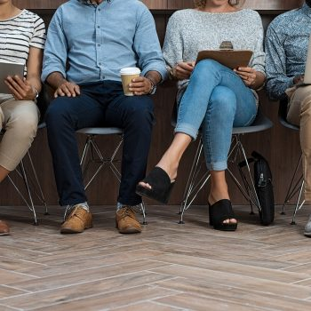 Multiethnic business people sitting on chair in a row for recruitment. Man and woman sitting while using laptop and tablets. Businessmen and casual businesswomen waiting in queue for job interview.